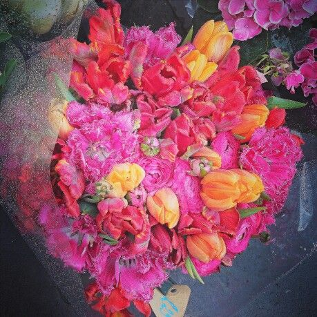 Pink anemones, orange tulips and coral parrot tulips in the rain