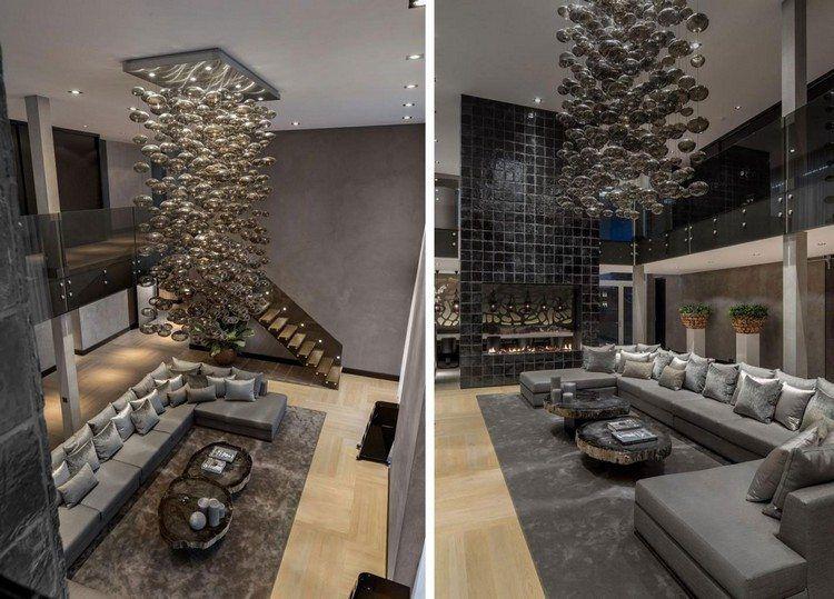 Salon double hauteur décoré en gris avec suspension design bulles