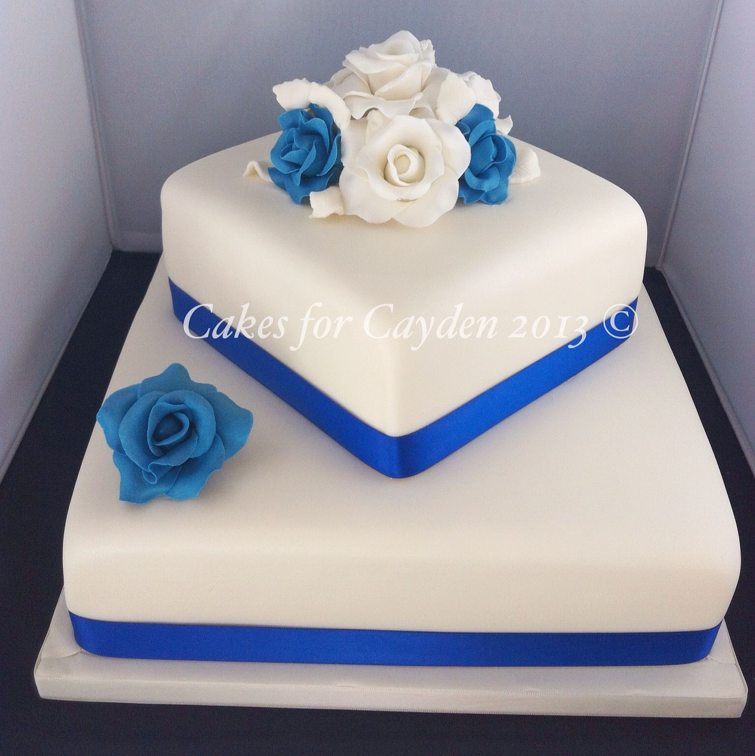 2 Tier Square Ivory And Royal Blues Wedding Cake With Hand Made Sugar Roses Square Wedding Cakes Tiered Wedding Cake Square Wedding Cakes Simple