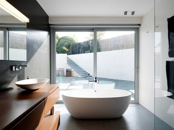 Deze badkamer kijkt uit op een ommuurd terras zonder inkijk. Dus kreeg de badkamer een groot schuifraam. Het vrijstaande bad mocht op een prominente plek in de ruimte. Nu nog wat planten binnen en buiten en je hebt je eigen oase.