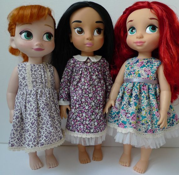 A pretty cotton dress with lace detail and pintuck front bodice. It has lace detail around the hem and pretty beads on the front. It closes at the back with velcro. The little cardigan has buttons at the front and a scalloped edge, knitted with soft merino wool.  Doll is not included.