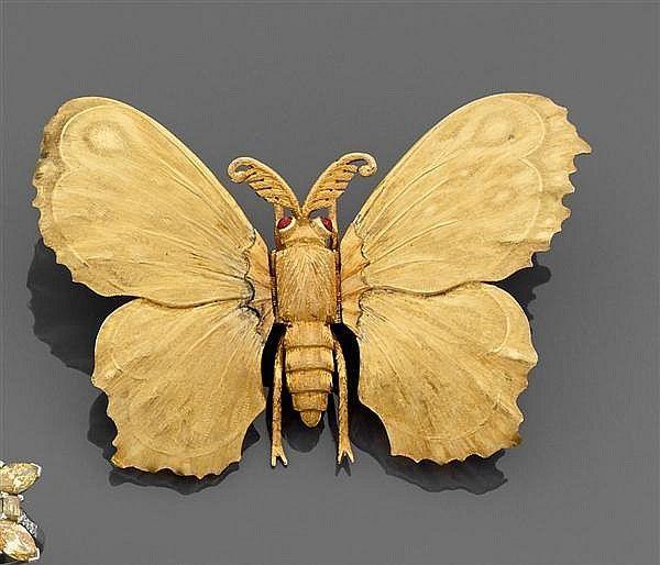 Mario Buccellati Années 1970 Clip Papillon Il est en ors de couleur ciselé et guilloché, les yeux sertis dÅfun cabochon de rubis. Les ailes sont articulées et actionnent les épingles.
