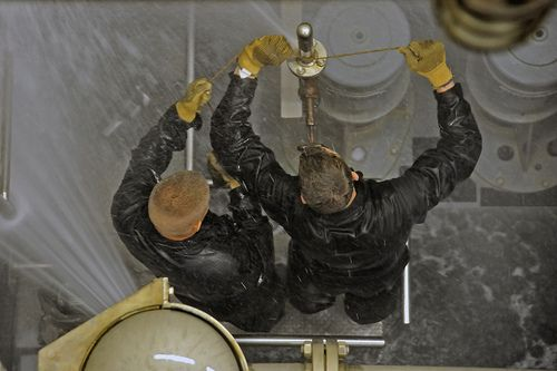 Midshipmen attempt to patch a leaking pipe in the damage control team wet trainer at Submarine Learning Center Detachment. Midshipmen visit the detachment as part of their summer orientation and participate in submarine training scenarios. Submarine Learning Center Detachment  currently supports training for San Diego based surface  submarine forces afloat in tactics, nuclear operations, individual and team skills,  plays an integral role in depot weapons handling and deployed force…