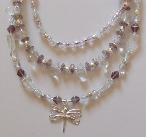 Three strand necklace featuring a dainty sterling silver dragonfly pendant. Various sizes and shapes of crystal quartz are accented with lavender