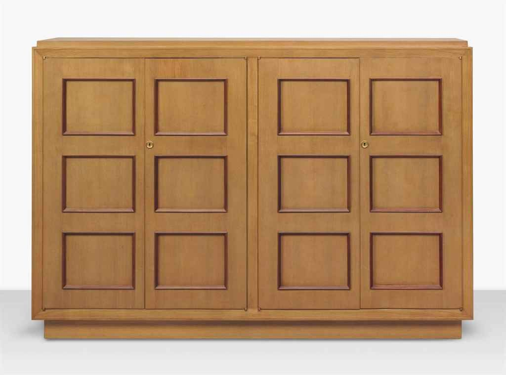 JACQUES ADNET (1900-1984)  A CABINET, CIRCA 1937  each compartment with three adjustable shelves, oak, beech, with brass details 48 3/8 (123 cm.) high, 70¾ in. (180 cm.) wide, 15¾ in. (40 cm.) deep