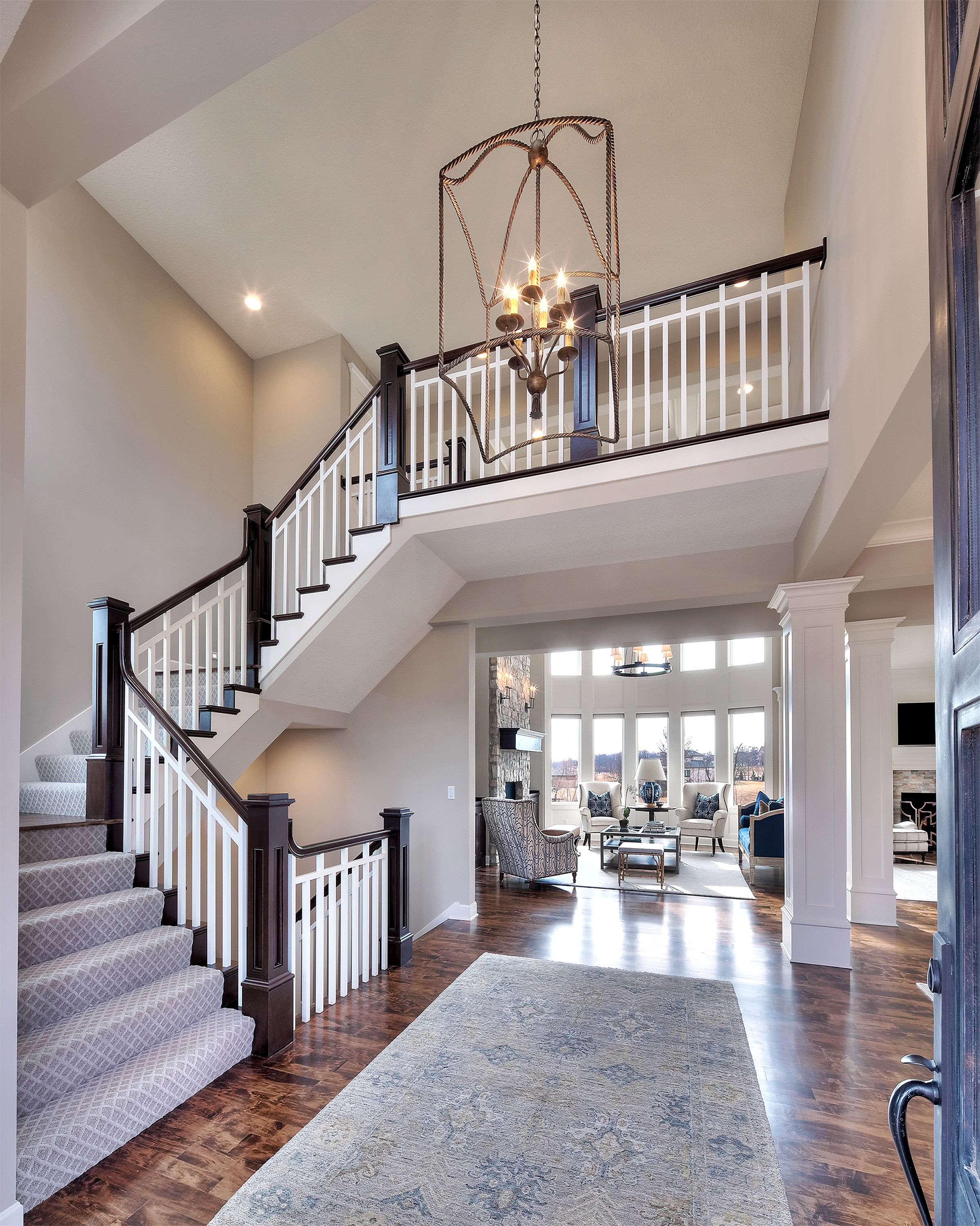 Entry curved staircase open floor plan overlook from for House plans with stairs in foyer