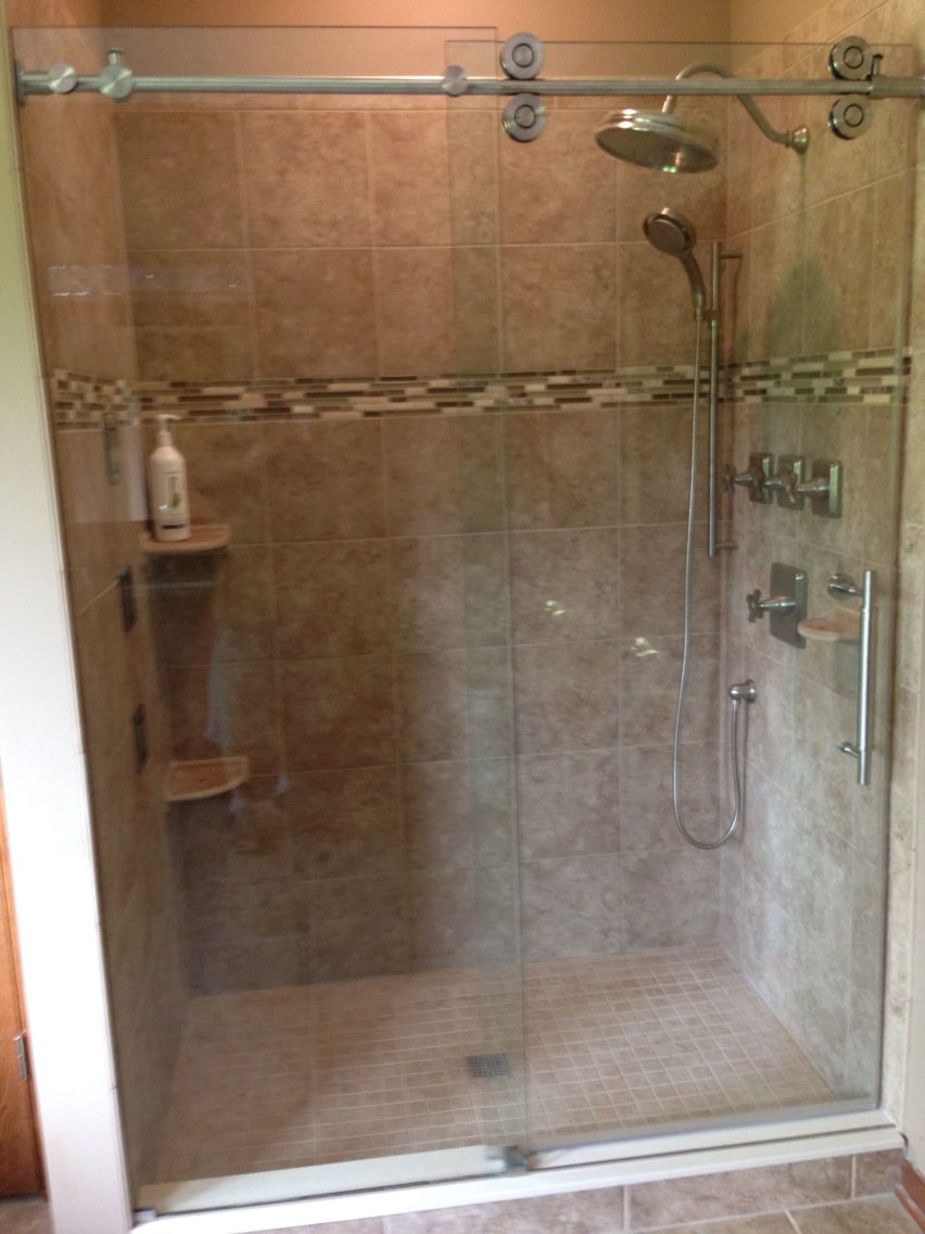 Euro style sliding shower enclosure with exposed roller wheels. One ...