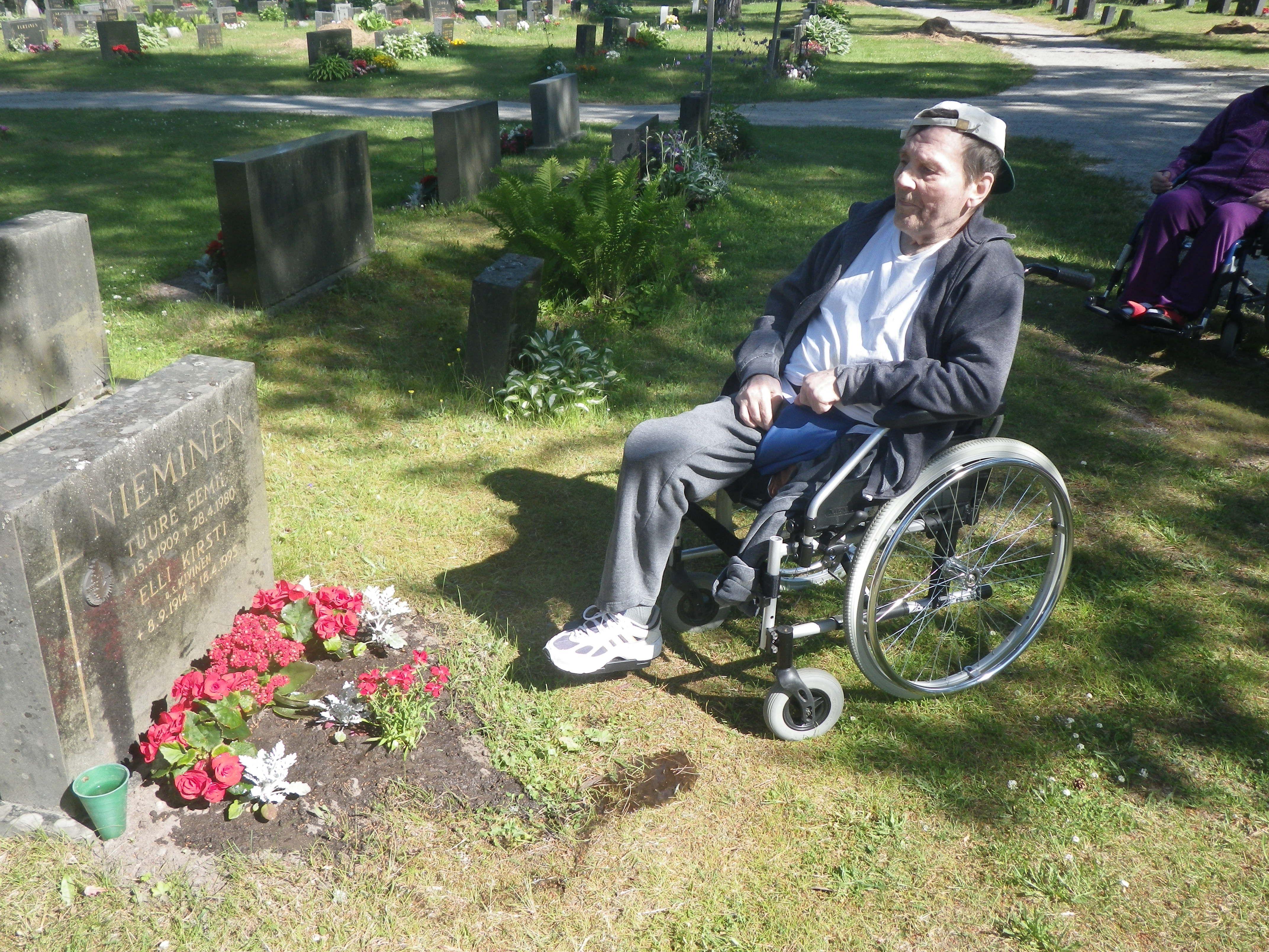 Vanhempien haudalle neilikoita istuttamassa