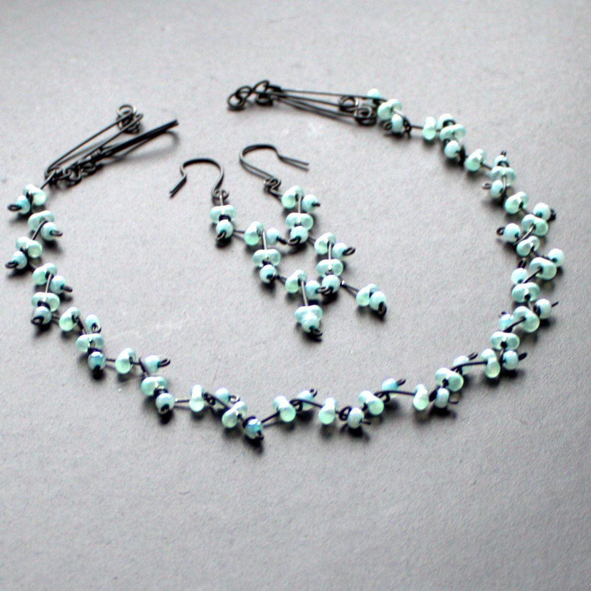 MENTOLOVÁ VĚTVIČKA Drátovaný náhrdelník a náušnice z černého 0,8 mm drátu a perleťově mentolových rokailových korálků a mašliček. Velikost mašličky je cca 0,6 cm Délka náhrdelníku je cca 52 cm, lze jej na požádání zkrátit či prodloužit. Lze vyrobit v jakékoliv jiné barvě. Délka náušnic je cca 7,5 cm. Šperk je vyroben pouze z drátu a korálků, bez ...