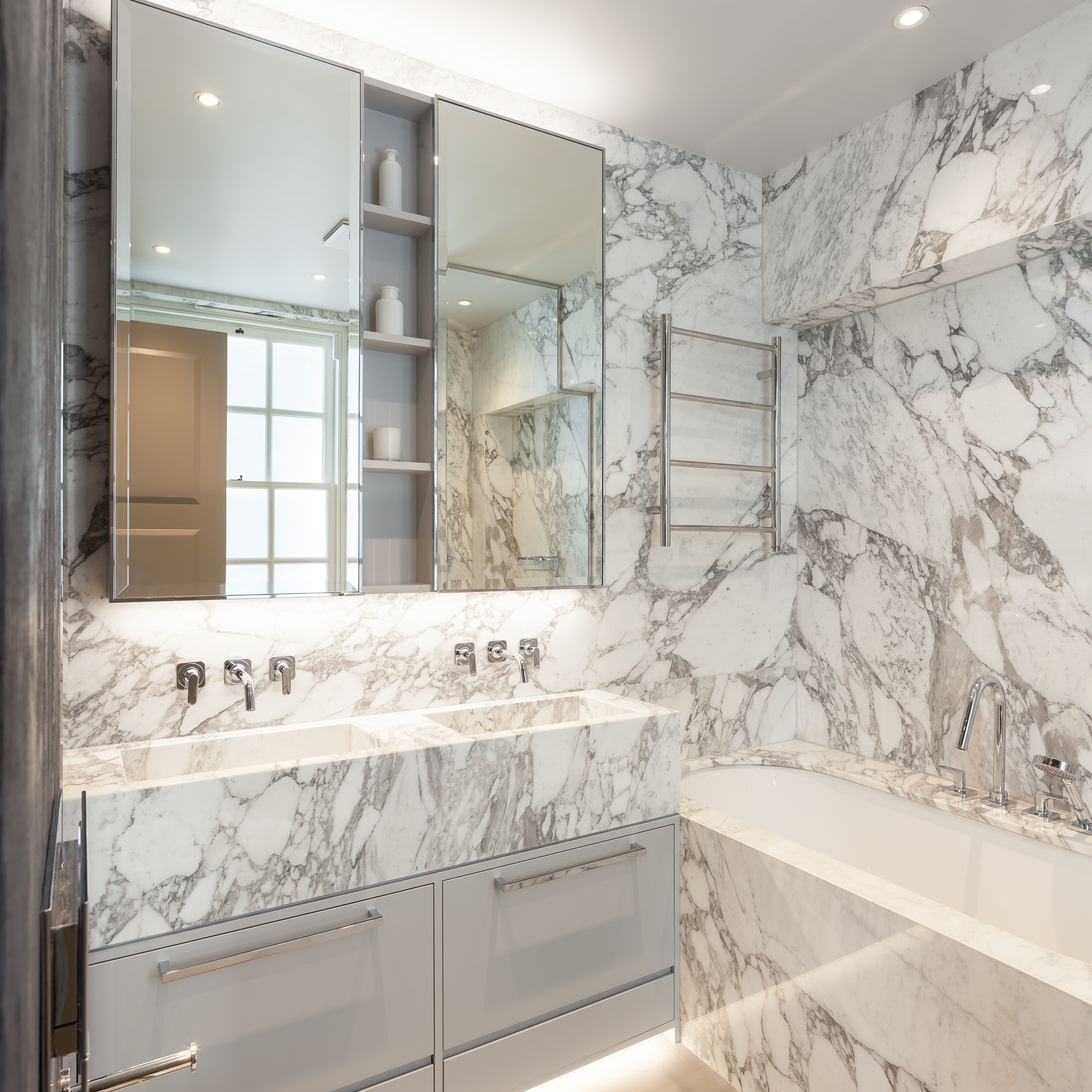 On this project the main family bathroom was fitted with white carrera marble and bespoke storage below the twin marble sinks