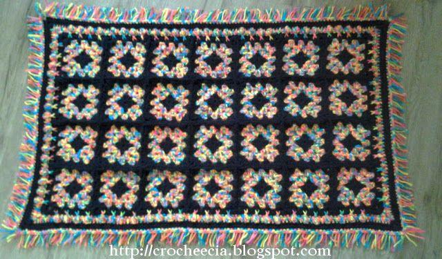 Tapete de Squares  Tapete de lã com o fio Cisne D'Primera preto e Multicolor. O contraste do fio multicolorido com o preto ficou bem bacana. 28 squares e, nas bordas, uma carreira de ponto pipoca e uma de franjas.
