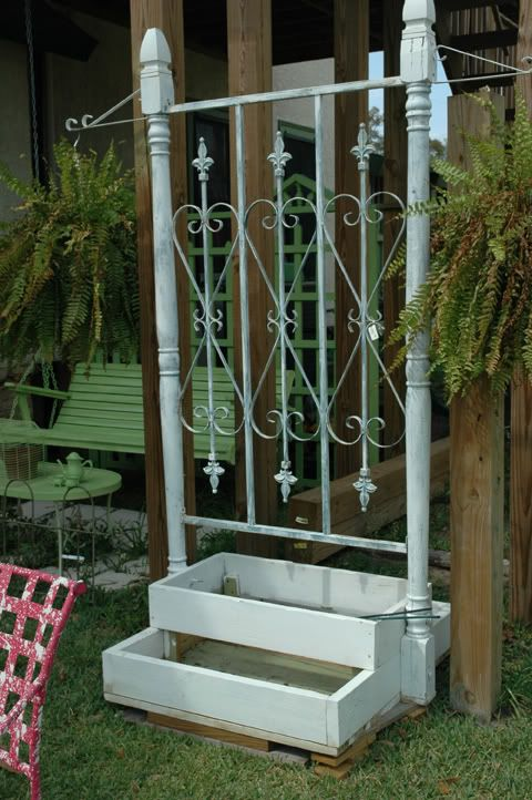 planting box with trellis ~ This one is just two upright porch posts fastened to a double sided window box. A bit of wrought iron (perhaps an old garden gate) between makes a trellis for whatever goes into the boxes, and they added brackets at the top of each post for hanging baskets