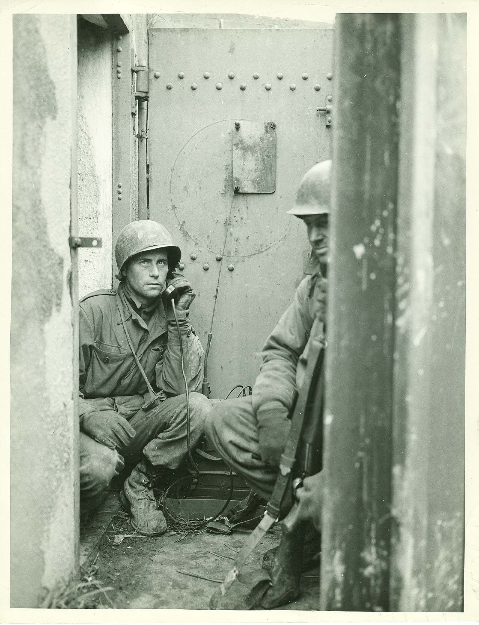 Date: 15 Dec 1944 Responsible agency / Photographer: United States Army Signal Corps. Tech 4 C. D. Bell. Description: Private First Class Joseph B. Wilkinson, Providence, RI, Radio Operator, and Sergeant Elmer J. Sullentrop, right, St. Louis, MO, a Field Artillery Observer, take up their post in an entrance of a Maginot Line pillbox, near Riedseltz, France. Company D, 62nd Armored Infantry Battalion, 14th Armored Division