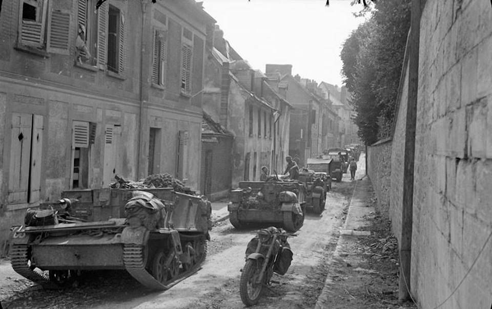 Universal carriers and other vehicles wait to cross the Seine at Vernon, 27 August 1944.