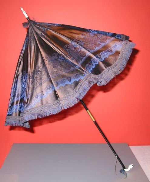 Parasol covered in figured silk, woven en disposition though I don't know if they were done with dress goods or patterns woven specifically for parasols