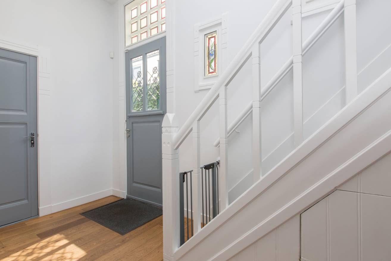 Grijze deuren witte kozijnen en muren gang