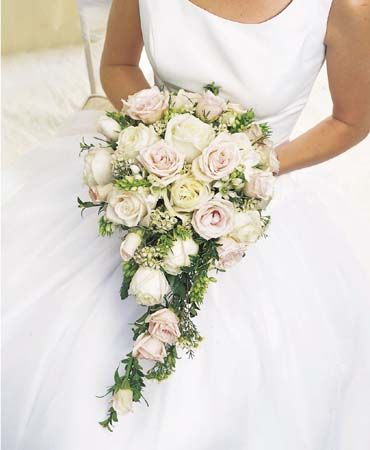 lovely bouquet is filled with white roses, white spray roses, star of Bethlehem, oregonia and wax flower.