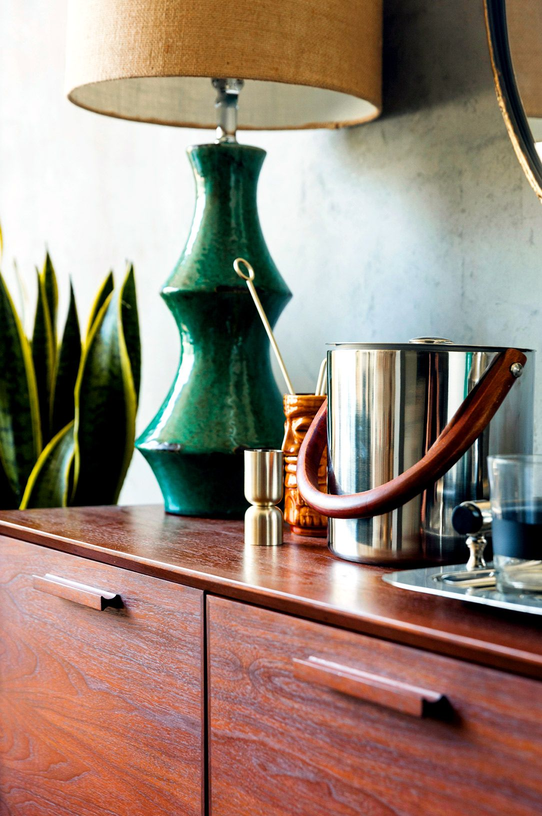 Green table lamp, ice bucket, and indoor plant