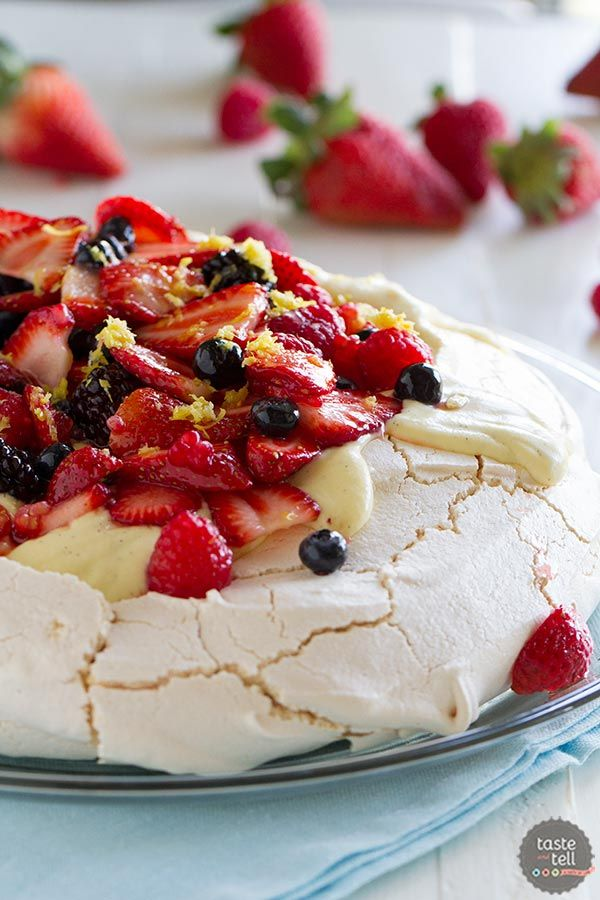 >A light and delicate meringue cake is topped with whipped cream, silky creme anglaise and lots of berries in this Pavlova Recipe with Fresh Berries.