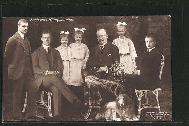 Sachsens Königsfamilie mit einem Hund im Garten sitzend