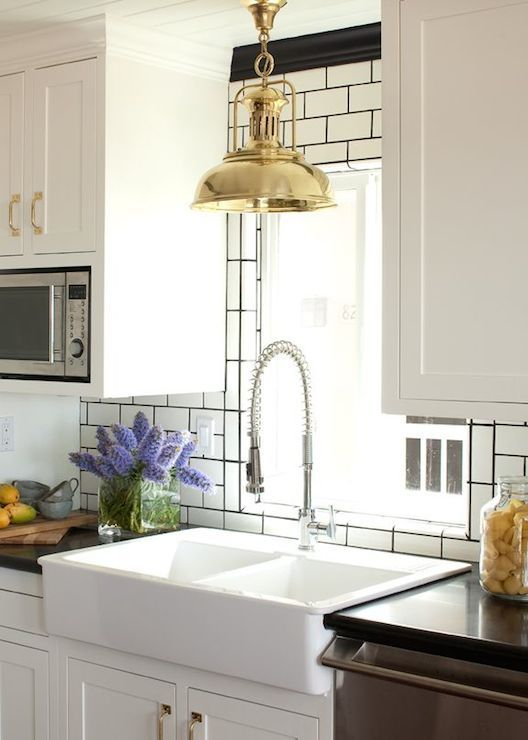 Stunning Kitchen With White Cabinets Paired With Brass Hardware Alongside Sleek Black Counters Which Fr Kitchen Makeover White Subway Tile Kitchen Inspirations