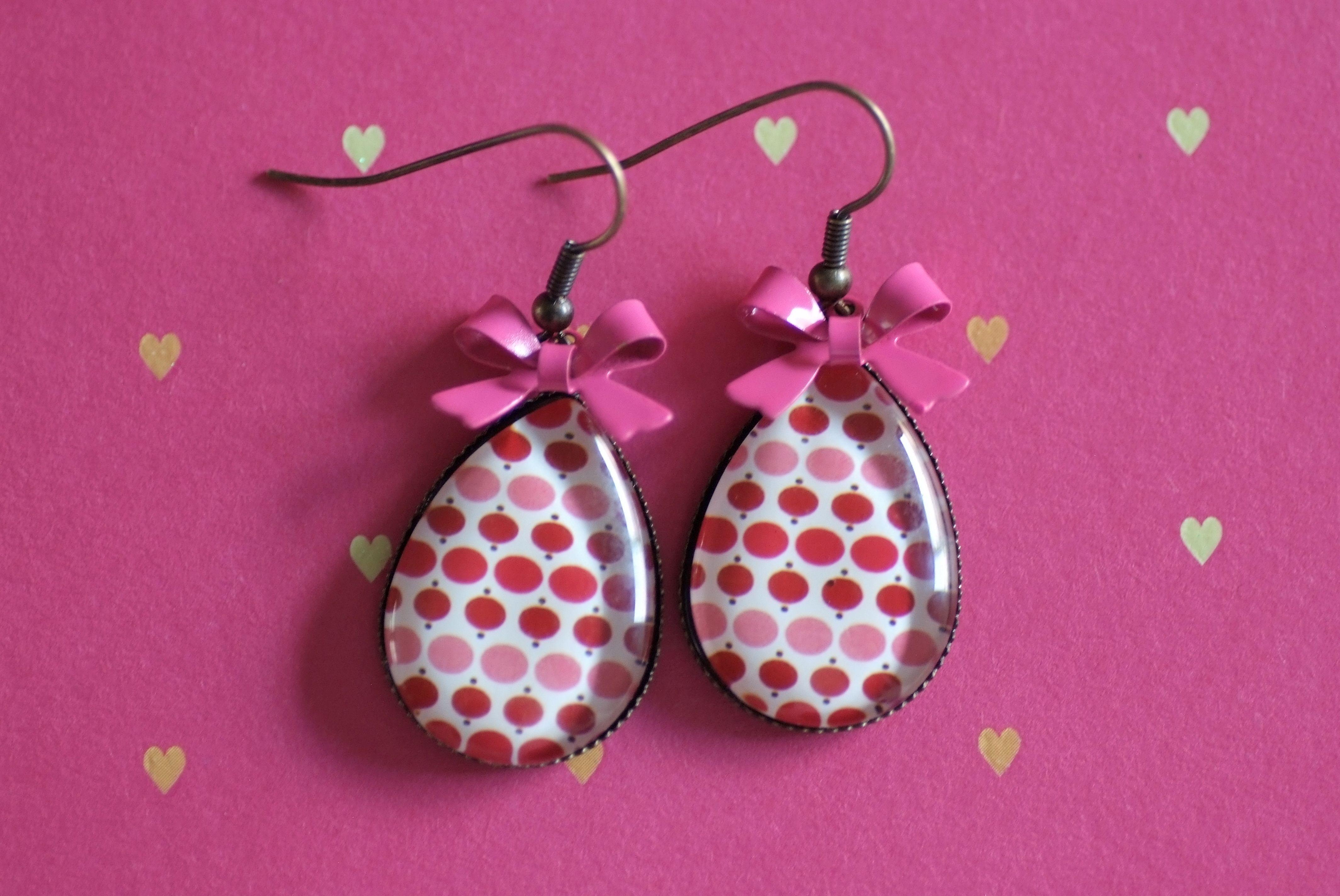 #D9 Handgemaakte oorbellen brons in druppelvorm met bollen roze/rood, witte achtergrond met zwarte stippen & een roze strikje! €9,00
