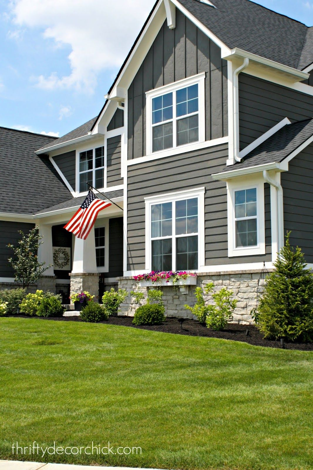 The exterior of our modern craftsman home exterior - White house with grey trim ...