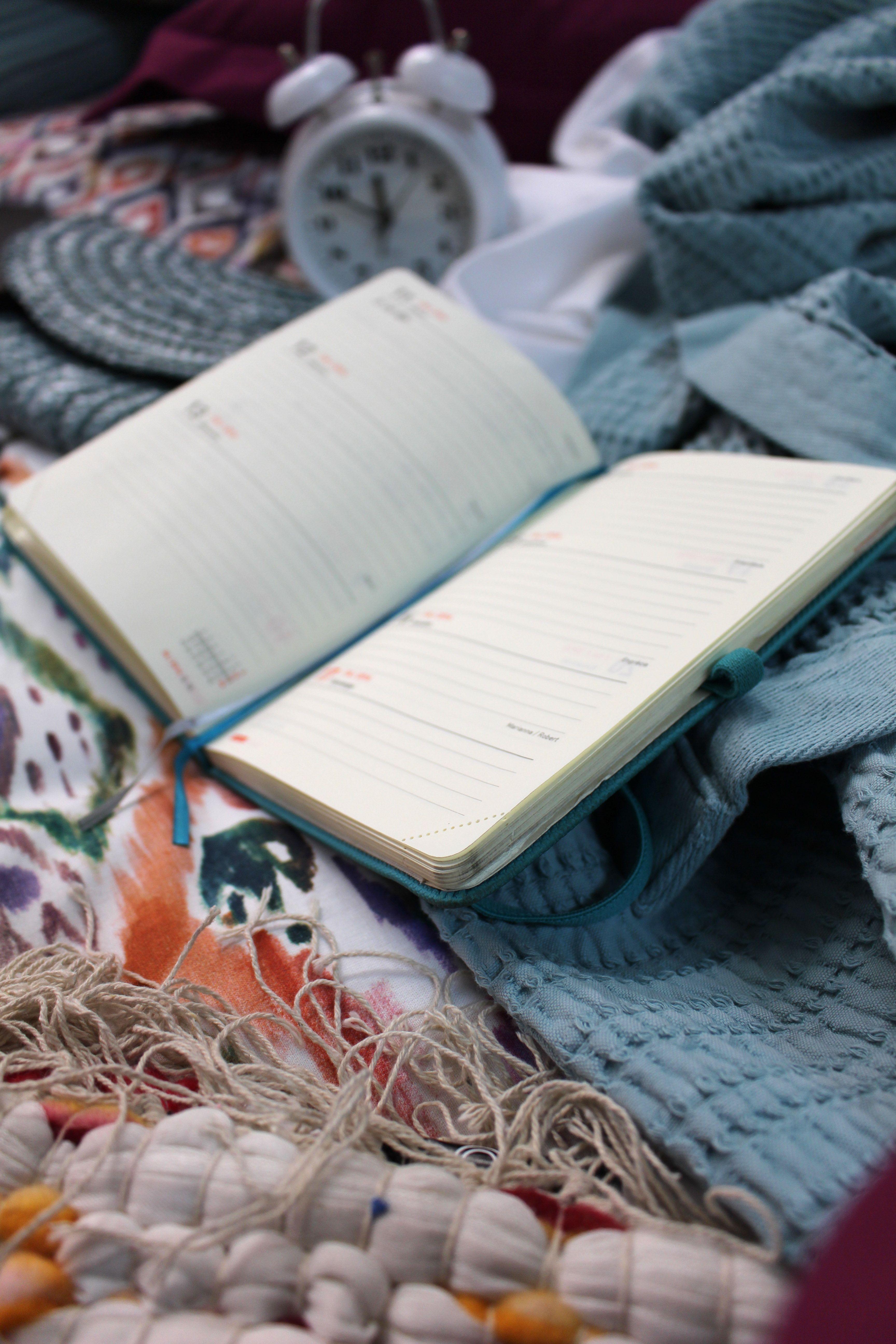 Cama desecha. Agenda abierta. Funda nórdica de colores estilo retro vintage. Unmade bed. Opened agenda. Duvet colorful retro vintage style.