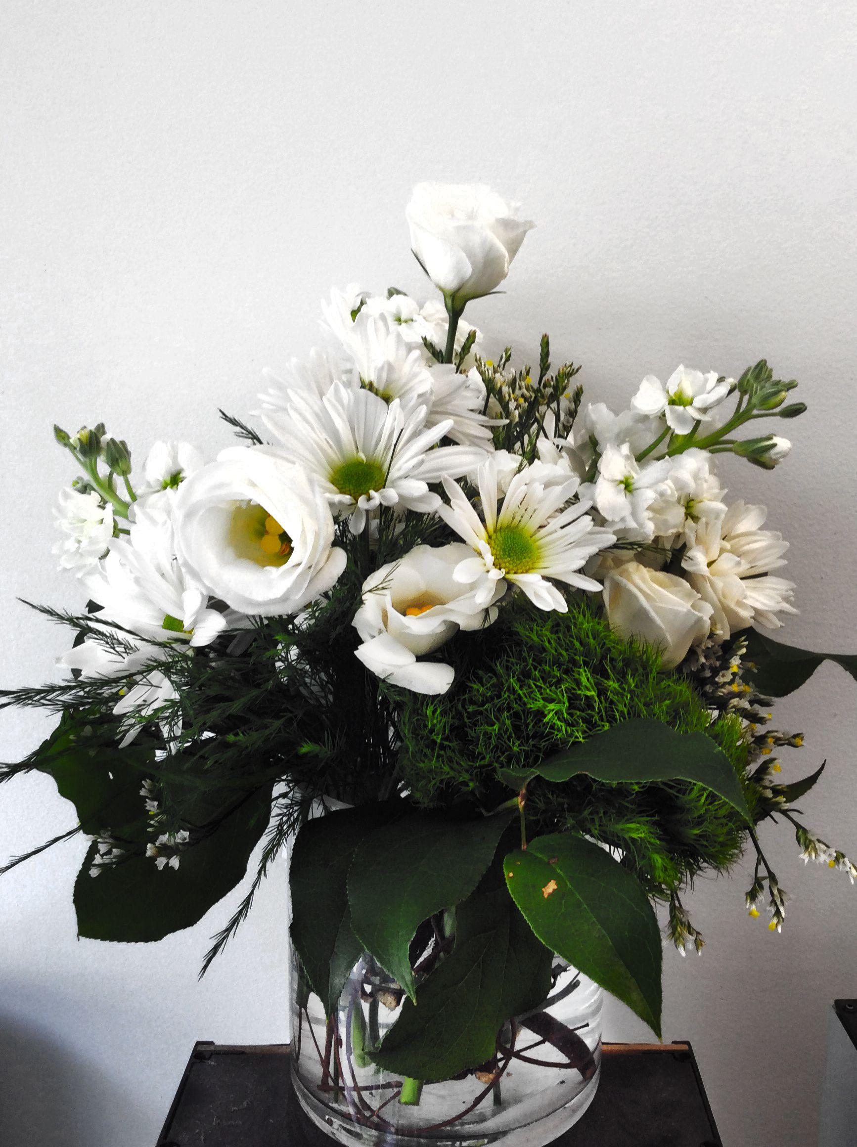 A Custom Floral Arrangement In A Cylinder Vase Designed By Flowers