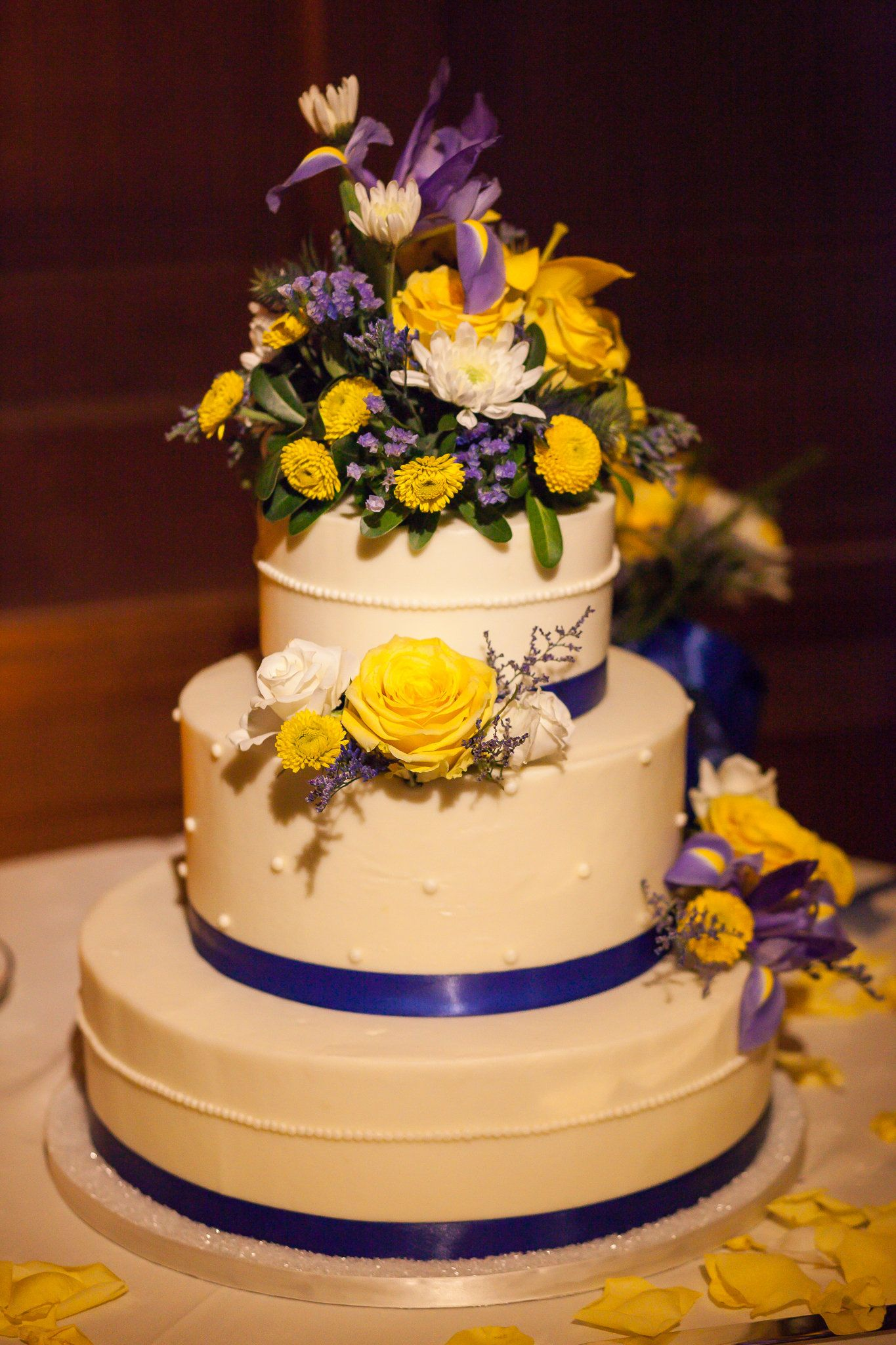 Three tier rounded wedding cake with royal blue ribbon and live ...