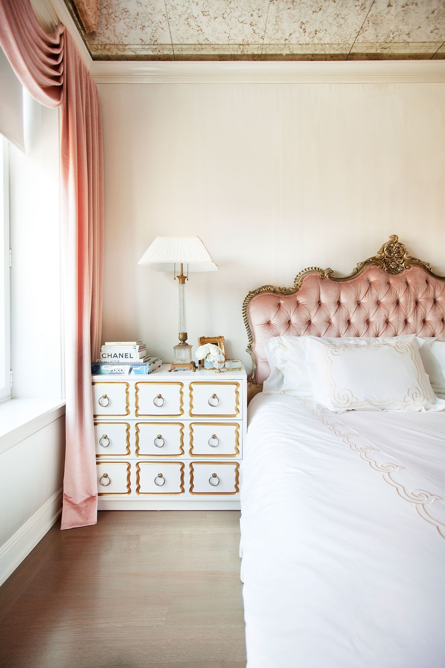 An Old World Inspired Bedroom With A Pink Upholstered Headboard Pink Tapestries And A White And Gold Dresser Chic Home Decor Bedroom Design Home Decor
