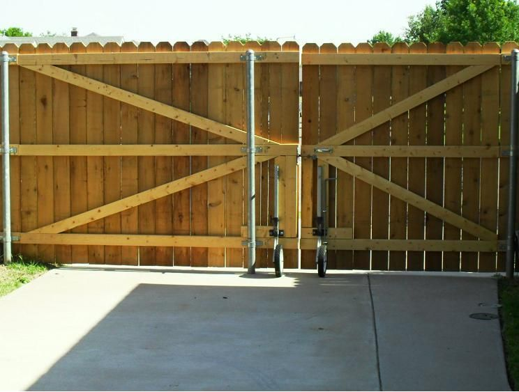 Wood driveway gate wheels big country fencing company for Wood driveway gate plans