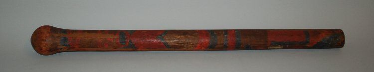 Staff, percussive musical instument(?) fake(?) made of a single piece of wood but split during manufacture and hollowed out. Crudely decorated on surface with red and blue painted designs.