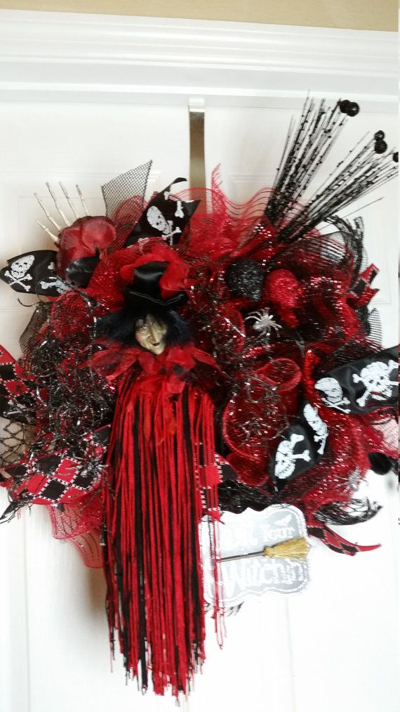 This Red/Black witch ruffle wreath features a Quit Your Witchin sign, spiders, rose with hand, skulls, decorative picks, and a witch.  W 19 H 21