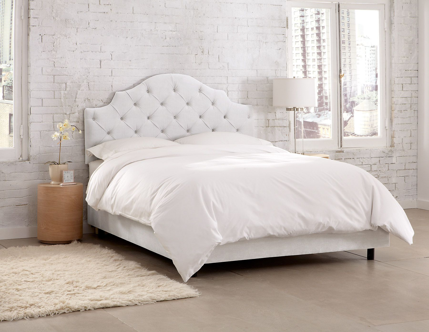 this elegant upholstered bed features diamond tufting on the  - house