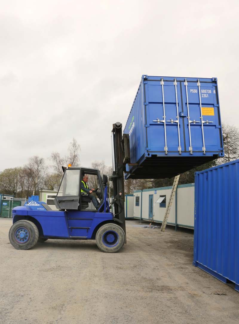 Dainton forklift moving shipping container stock at our
