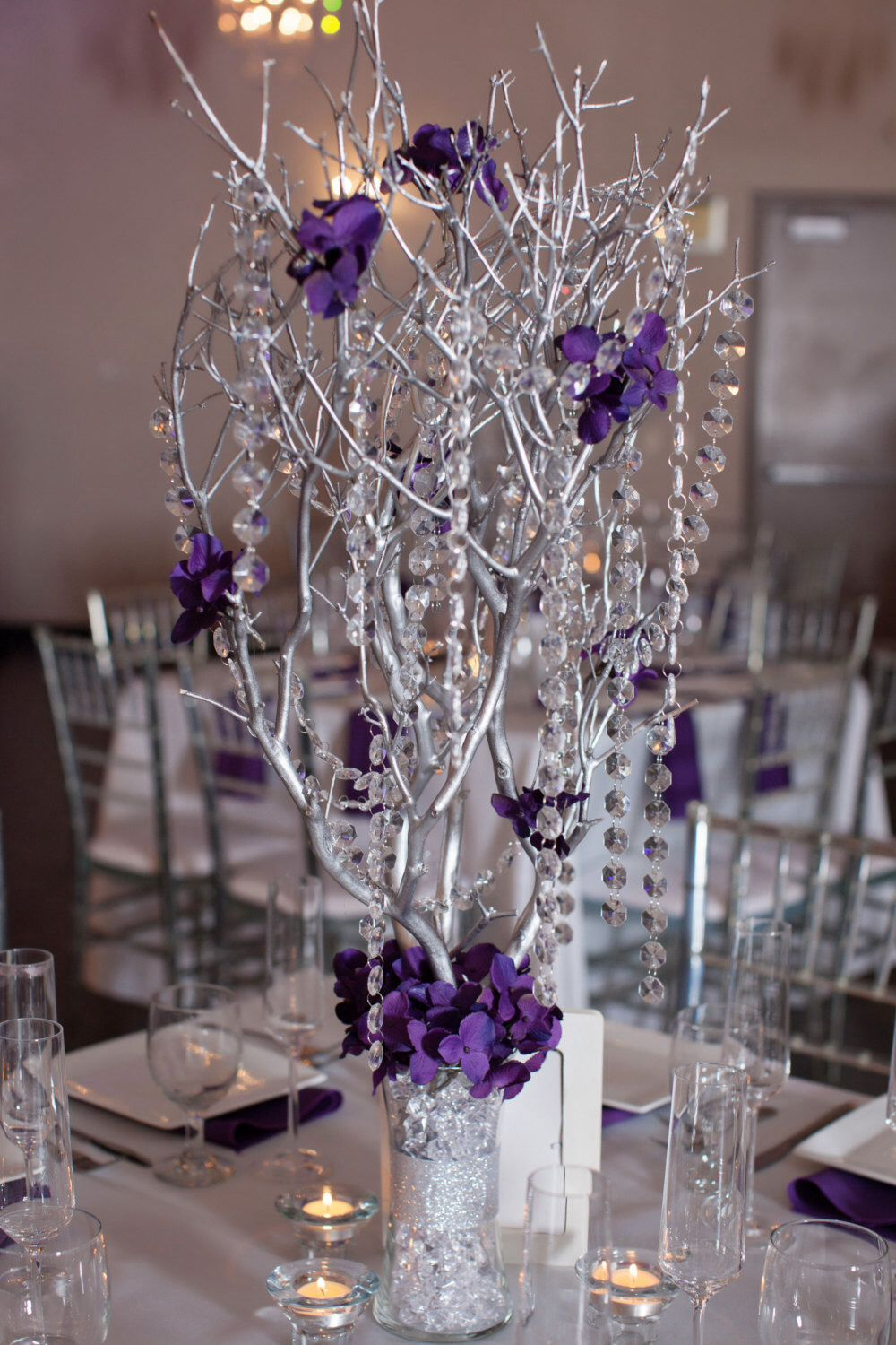 Spray painted branches, dangling crystals with a touch of purple flowers |  Wedding centerpieces diy, Barn wedding decorations, Silver wedding  decorations
