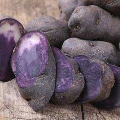 A sliced purple potato on a cutting board.