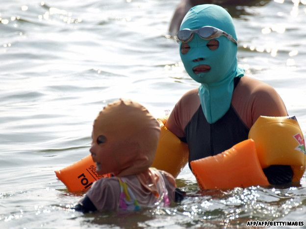 """beachgoers in Quingdao, China don """"facekinis"""" in an effort to avoid the sun, jellyfish and sharks"""