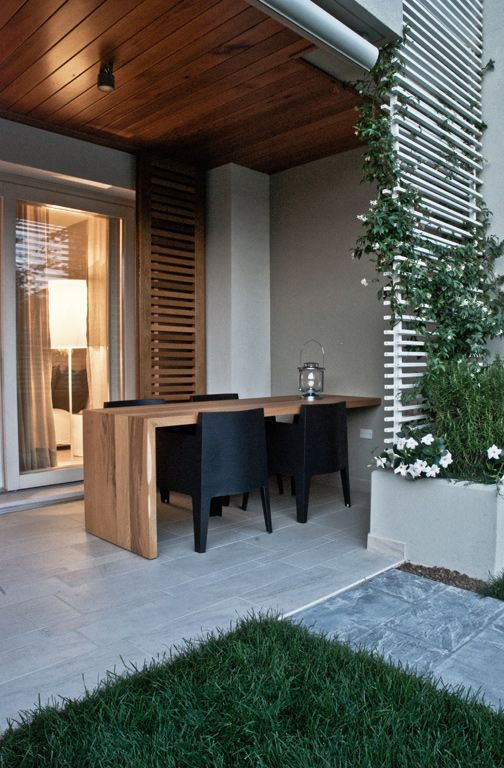 warm shades of oak contemporary trellis and table set against black and white outdoor dining