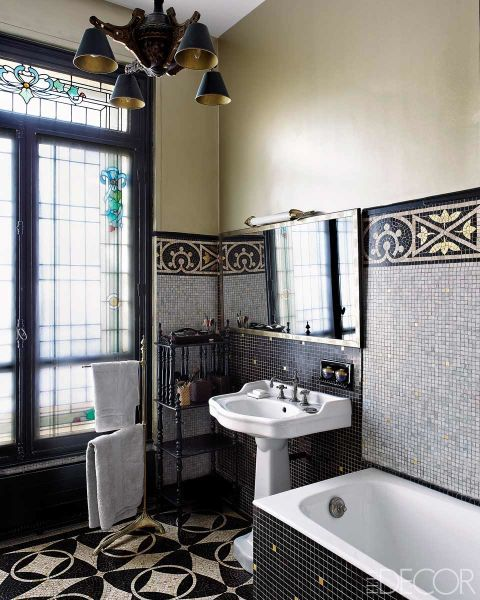 The opulent tiles on the walls and floor of this bathroom make it the perfect oasis. The marble mosaic tiles on the walls and floor of the master bath are original to the apartment; the 19th-century Chinese-style light fixture was found at a flea market in L'Isle-sur-la-Sorgue. See the rest of the home.   - ELLE.com
