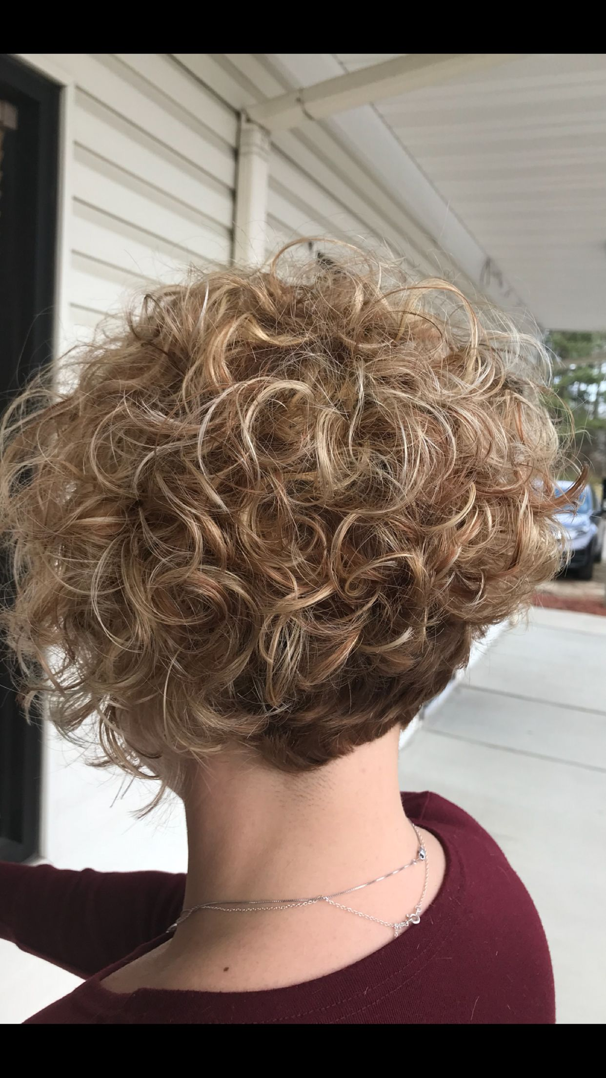 Short curly angled bob with root shadow and blonde balayage #curlshorthair