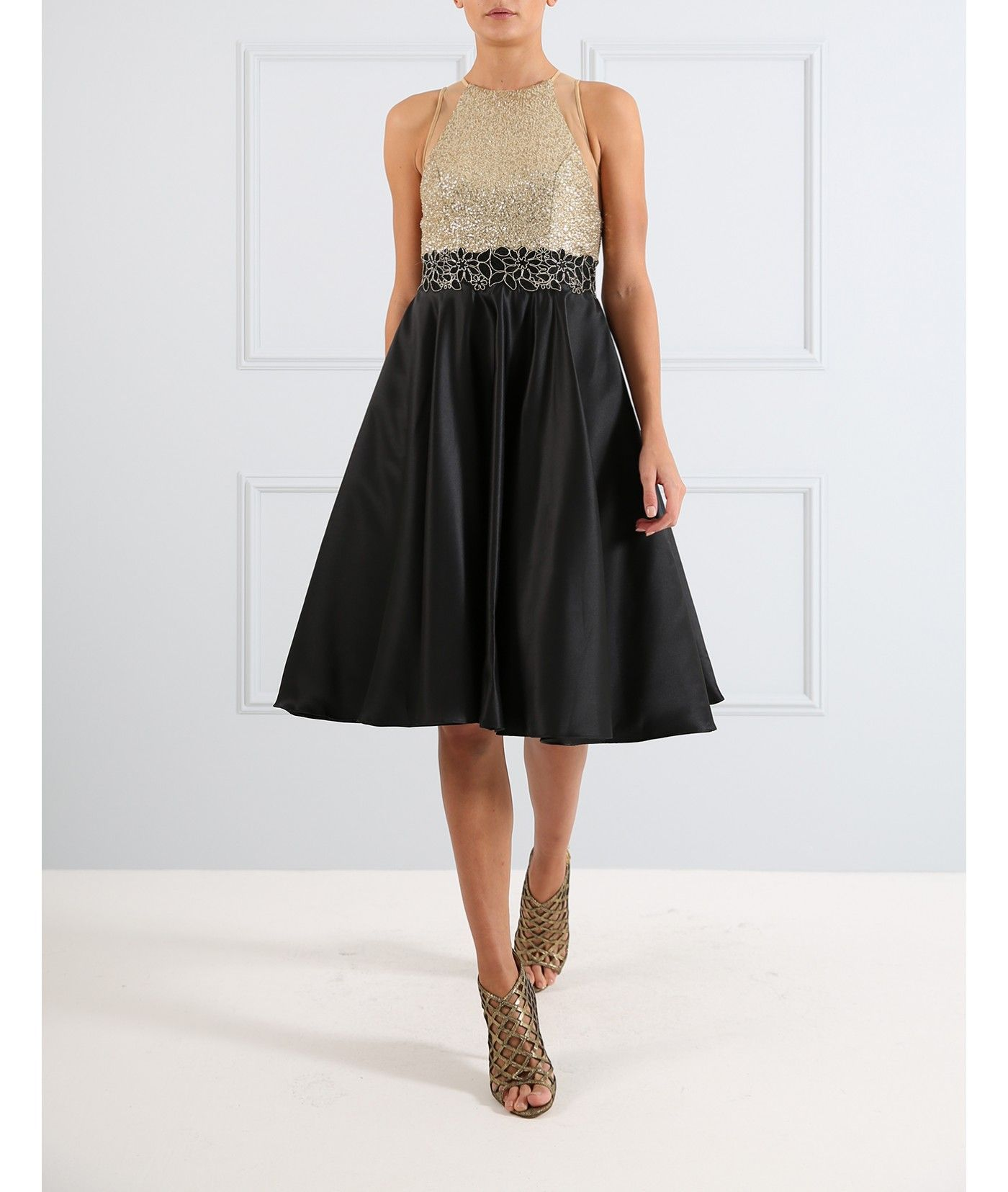 Whether you're heading to prom or a black-tie event, our black and gold full-skirt dress is a must-have. Featuring a black satin skirt and sparkling gold sequin bodice with floral applique detailing, be the belle of the ball this season.