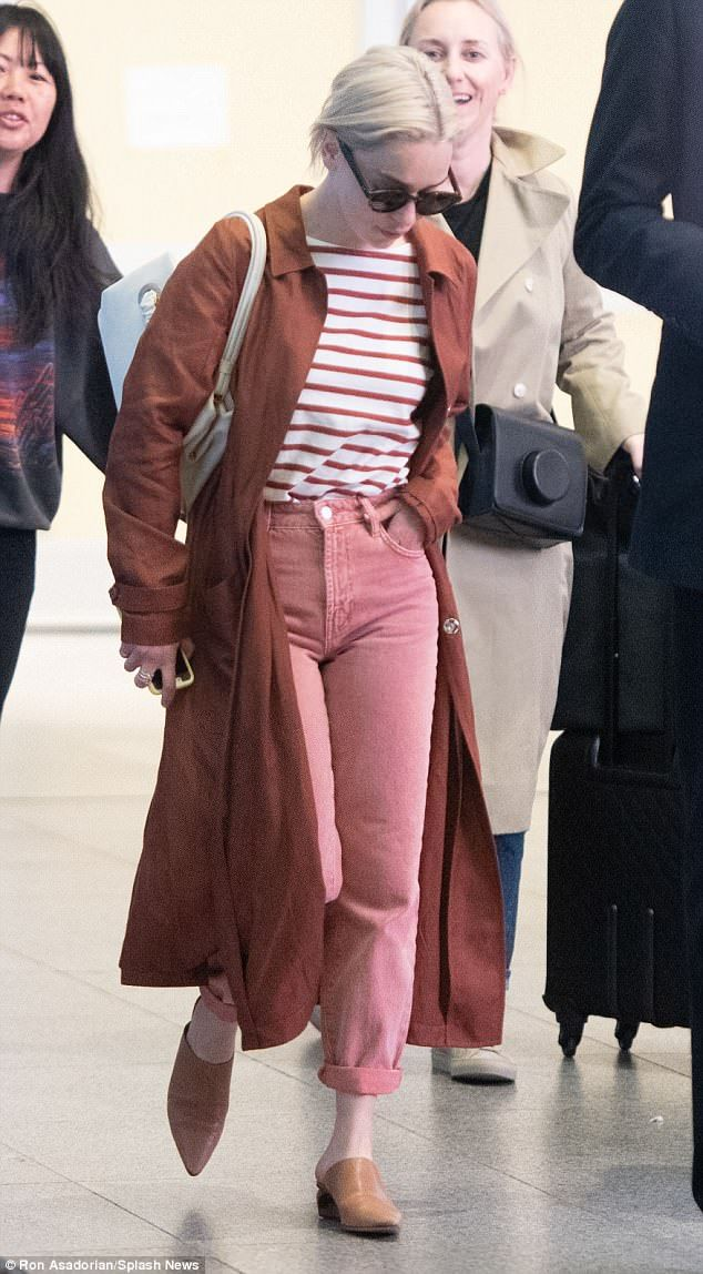 Emilia Clarke looks effortlessly chic in pink jeans and rust coat #emiliaclarke