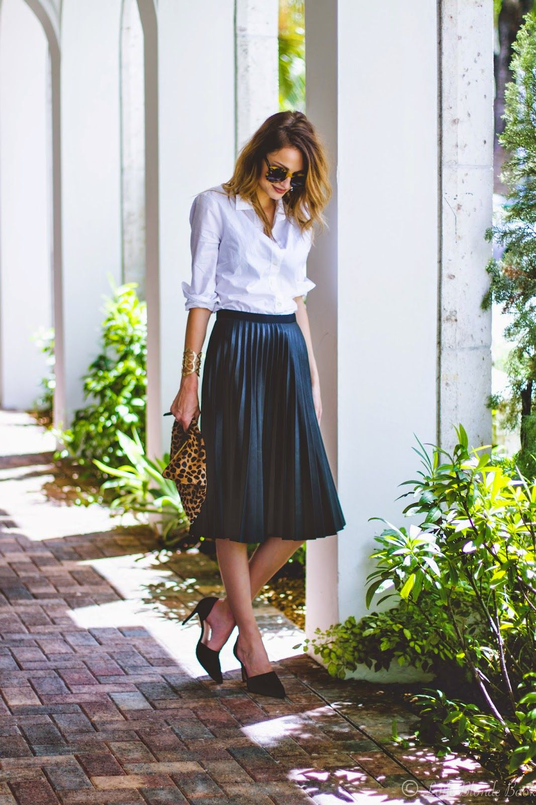 0cba66450 Taylor Morgan has created a stylish and sophisticated look by combining a  bottle green pleated skirt with heels and a white shirt. Add some striking  leopard ...
