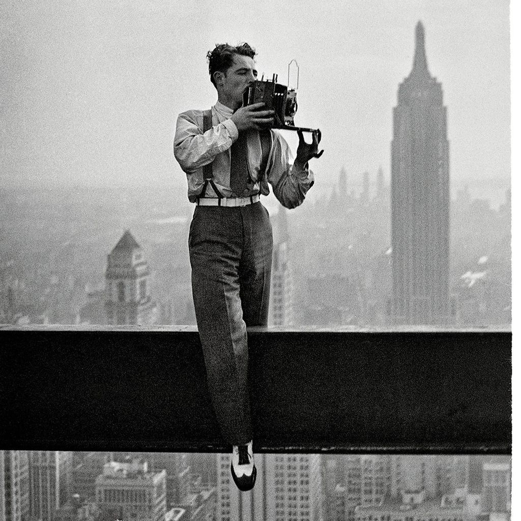 """The Dapper Daredevil who Documented America's Skyline in the Making - Where do I start with this photograph? The dapper shoes? The Gene Kelly stance? The delicate ease with which he's holding that enormous camera? Or the fact that all of this is happening at some unthinkable height above the streets of New York? This handsome fellow is American photographer, Charles C. Ebbets, the very same Charles C. Ebbets who captured one of the most iconic images of all time, """"Lunchtime atop a Skyscraper""""..."""