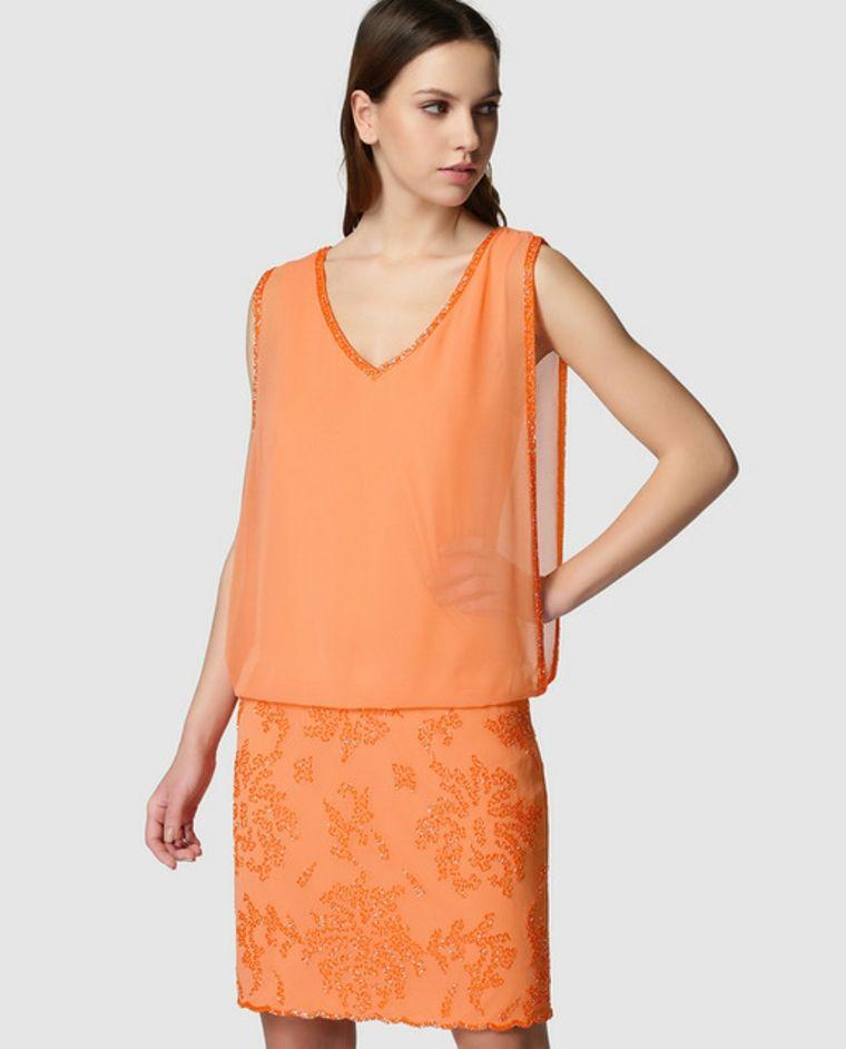 82d93fd45901 Donna con un vestito di colore arancione, top trasparente e parte inferiore con  pizzo