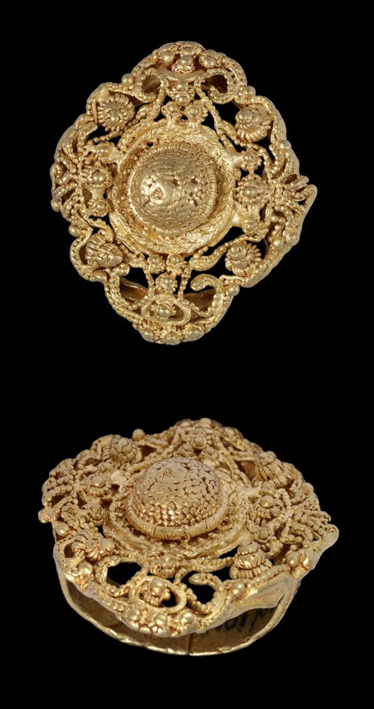 Africa | Lost wax casting in gold of a finger-ring consisting of an oval open-work bezel and a patterned band. The centre has a solid plain raised circular boss which is surrounded by an intricate oval symmetrical pattern of open-work scrolls and arabesques punctuated with raised dots. | Asante people, Ghana | 19th - 20th century || {7.19}