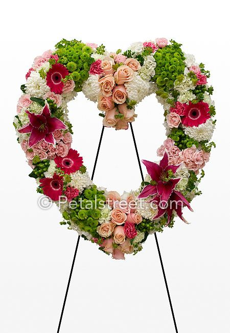 Funeral heart flower form with magenta lillies and daisies, and pink roses, and green button mums.