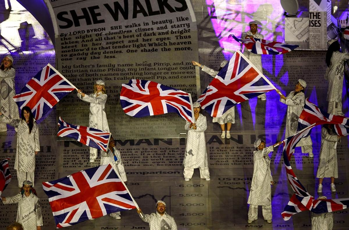 Performers fly Union Jack flags during the Closing Ceremony
